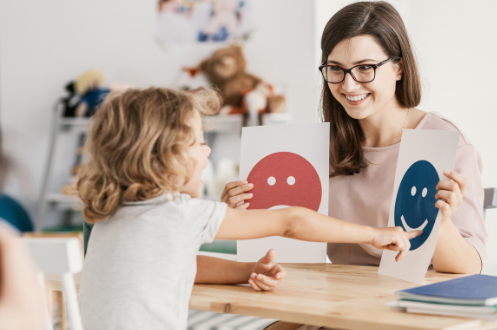 Teacher holding color face cards in front of young child pointing at cards